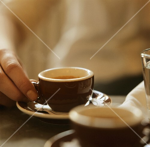 Hand holding an espresso cup on table