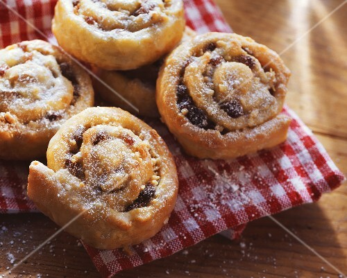 Raisin snails with icing sugar on checked cloth
