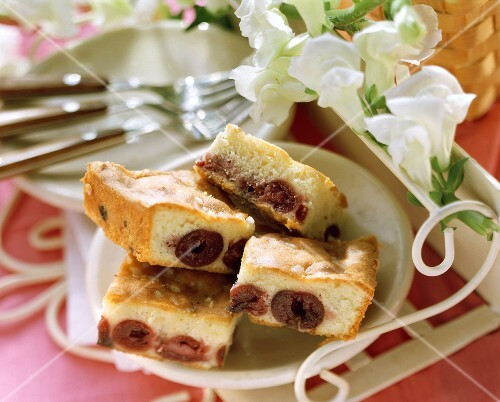 Pieces of cherry cake on white plate; white flowers