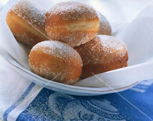 Fresh doughnuts with sugar on white plate