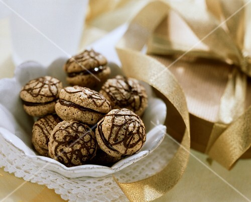 Mocha macaroons in a bowl; box with a gold bow