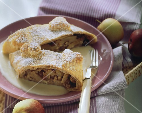 Apple strudel with nuts and icing sugar on plate