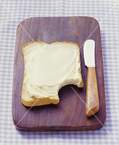 Buttered bread on bread board, a bite taken