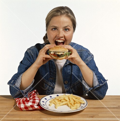 Model eating hamburger with chips