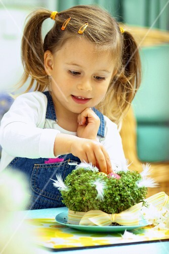 Small girl with cress Easter nest