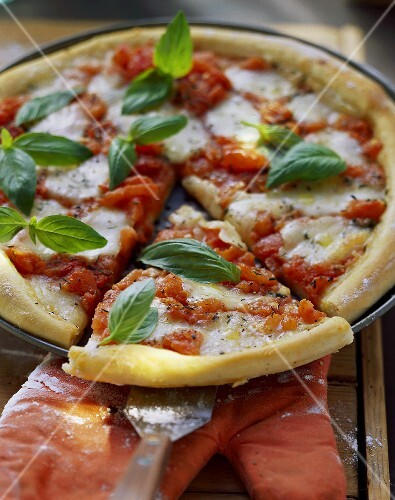 Pizza Margherita with basil (a piece cut)