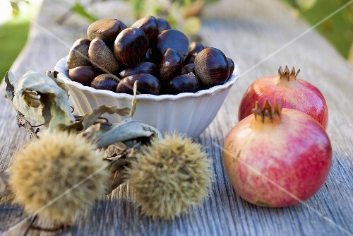 Sweet chestnuts and pomegranates on wooden table
