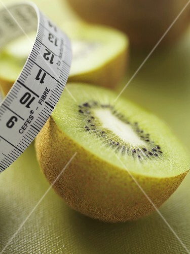Two halves of a kiwi fruit with tape measure
