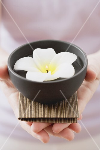Woman holding bowl of water with flower candle