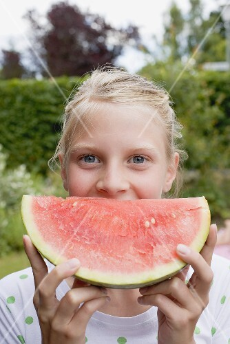 Girl holding a slice of watermelon out of doors