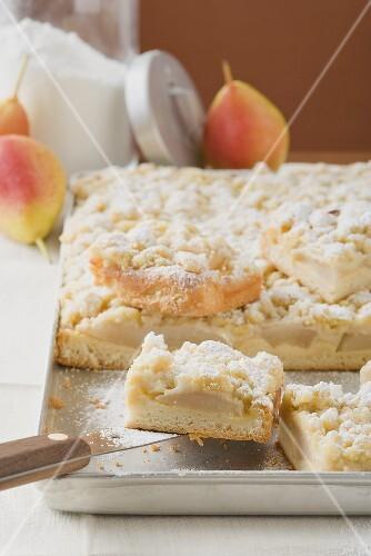 Pear crumble cake on baking tray (detail)
