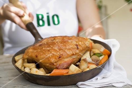 Woman holding pan of organic roast pork & root vegetables