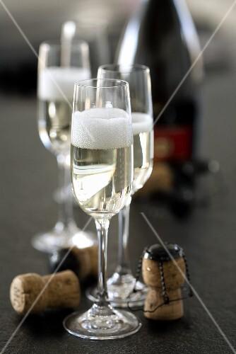Sparkling wine glasses, corks and bottle of sparkling wine