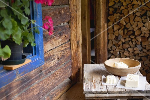 Home-made farmhouse butter on wooden table outside an Alpine chalet