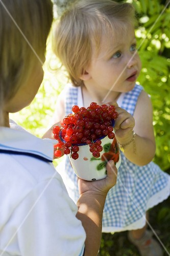 Girl and boy with redcurrants in the open air