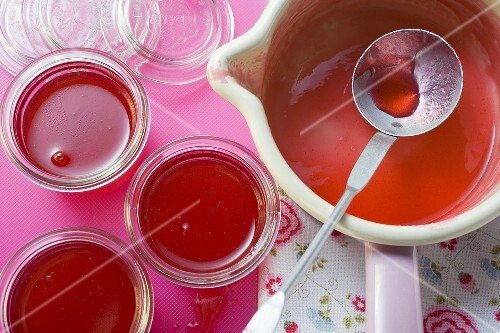 Redcurrant jelly in a pan and three jars
