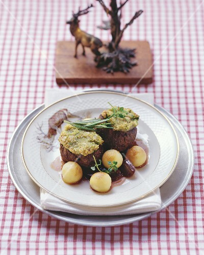 Venison medallions with herb and nut crust and grape sauce