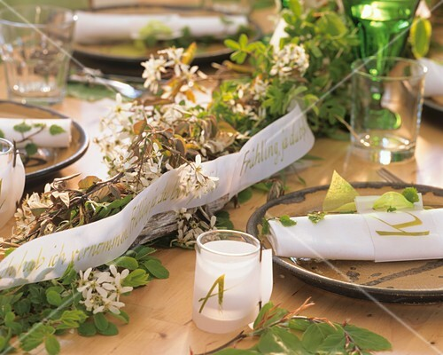 Laid table with spring theme with flowering branches & ribbon