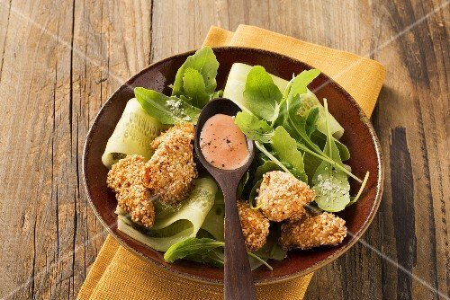 Rocket salad with sesame chicken nuggets