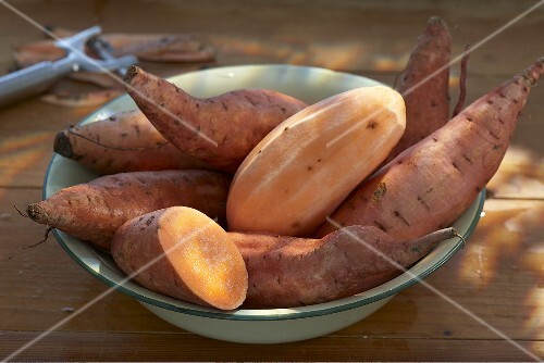 Sweet potatoes in a bowl, whole, halved and peeled