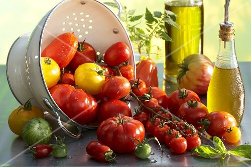 Various types of tomatoes with a colander