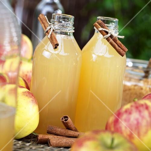 Cloudy apple juice in glass bottles, fresh apples, cinnamon sticks