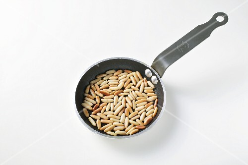 Toasted pine nuts in a frying pan