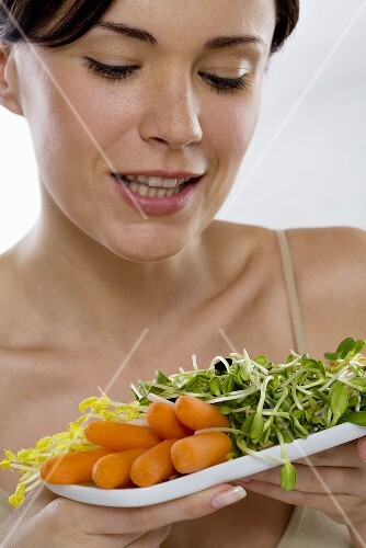 Young woman holding plate of raw vegetable salad