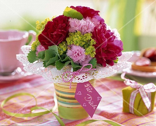 A posy of roses, pinks and lady's mantle with gift tag
