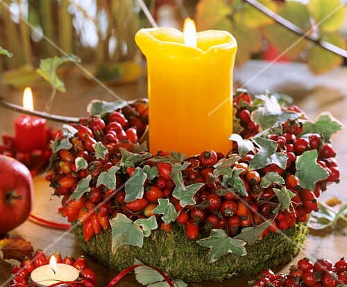 Autumn wreath of rose hips and ivy with candle