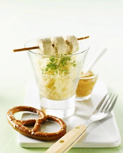 Sauerkraut im Glas mit Weißwurstscheiben und Salzbrezel