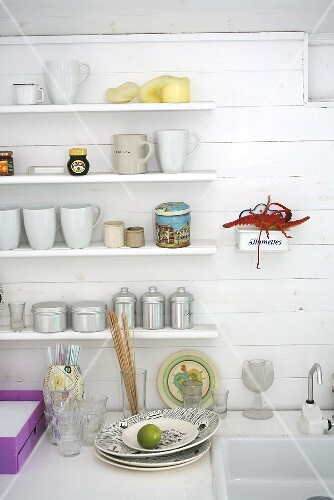 Kitchen utensils on white shelves in a beach house