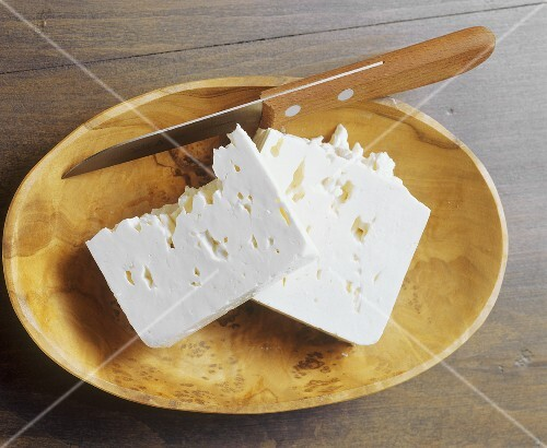 Feta with knife in a wooden bowl