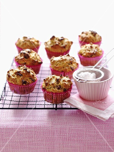 Lots of apple and cranberry muffins on a wire rack with icing sugar