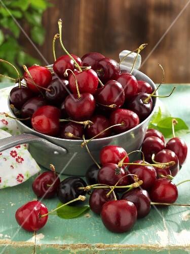 Fresh cherries in and beside pan