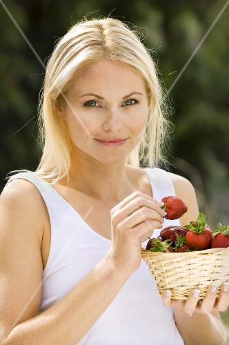 Blond woman holding basket of strawberries