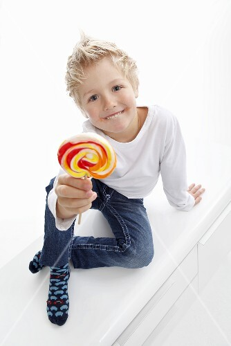 A little boy holding a lolly