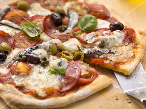 Tomato pizza with salami, gorgonzola, sardines and olives