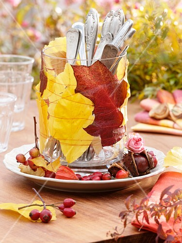 Autumn leaves and cutlery in glass (table decoration)