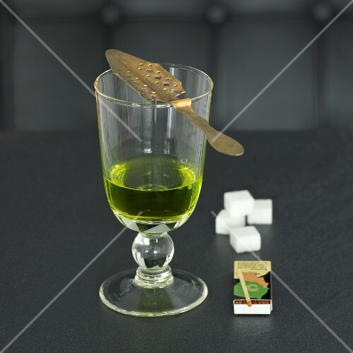 Glass of absinthe with spoon, matches and sugar cubes