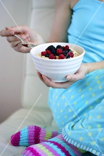 Woman eating muesli with berries