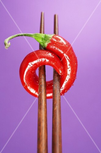 A chilli on chopsticks, purple background