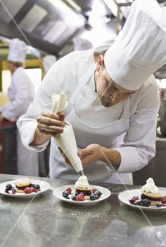 Chef piping cream onto berry desserts