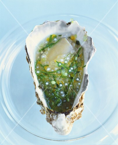 A marinated oyster on a glass plate