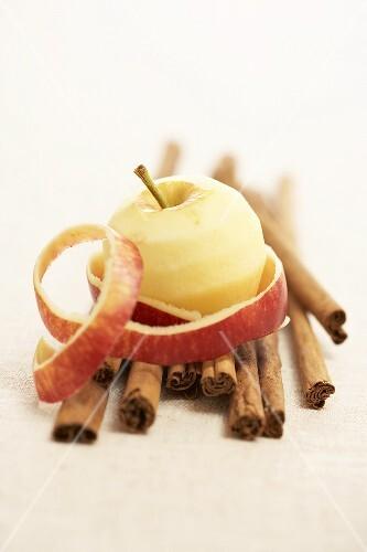 A peeled apple on cinnamon sticks