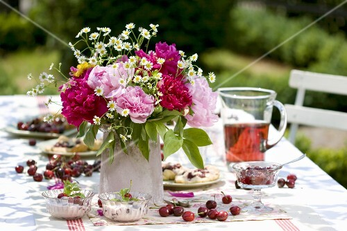 Cherry desserts and vase of flowers on table in garden