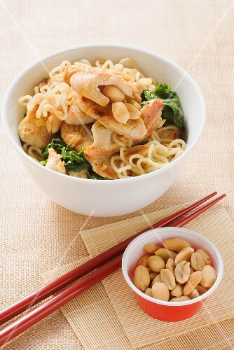 Fried noodles with turkey breast, spinach and peanuts
