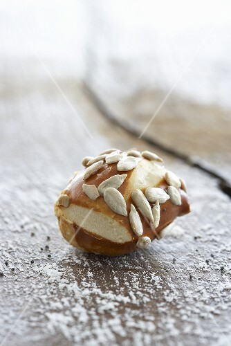 A lye bread roll with sunflower seeds on a wooden surface