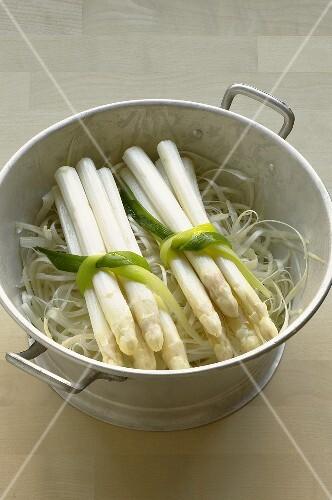 Two bundles of asparagus on asparagus peelings in colander