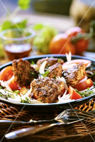 Grilled meat patties on tomato and onion salad